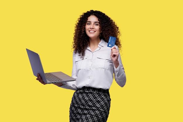 巻き毛の笑顔の女性は黄色の孤立した背景の上にラップトップコンピューターとクレジットカードを保持します。