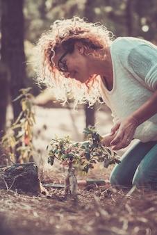 Улыбающаяся женщина с вьющимися волосами, сажающая новое дерево в лесу или саду. счастливая женщина заботится о растении в природе. женщина празднует день земли