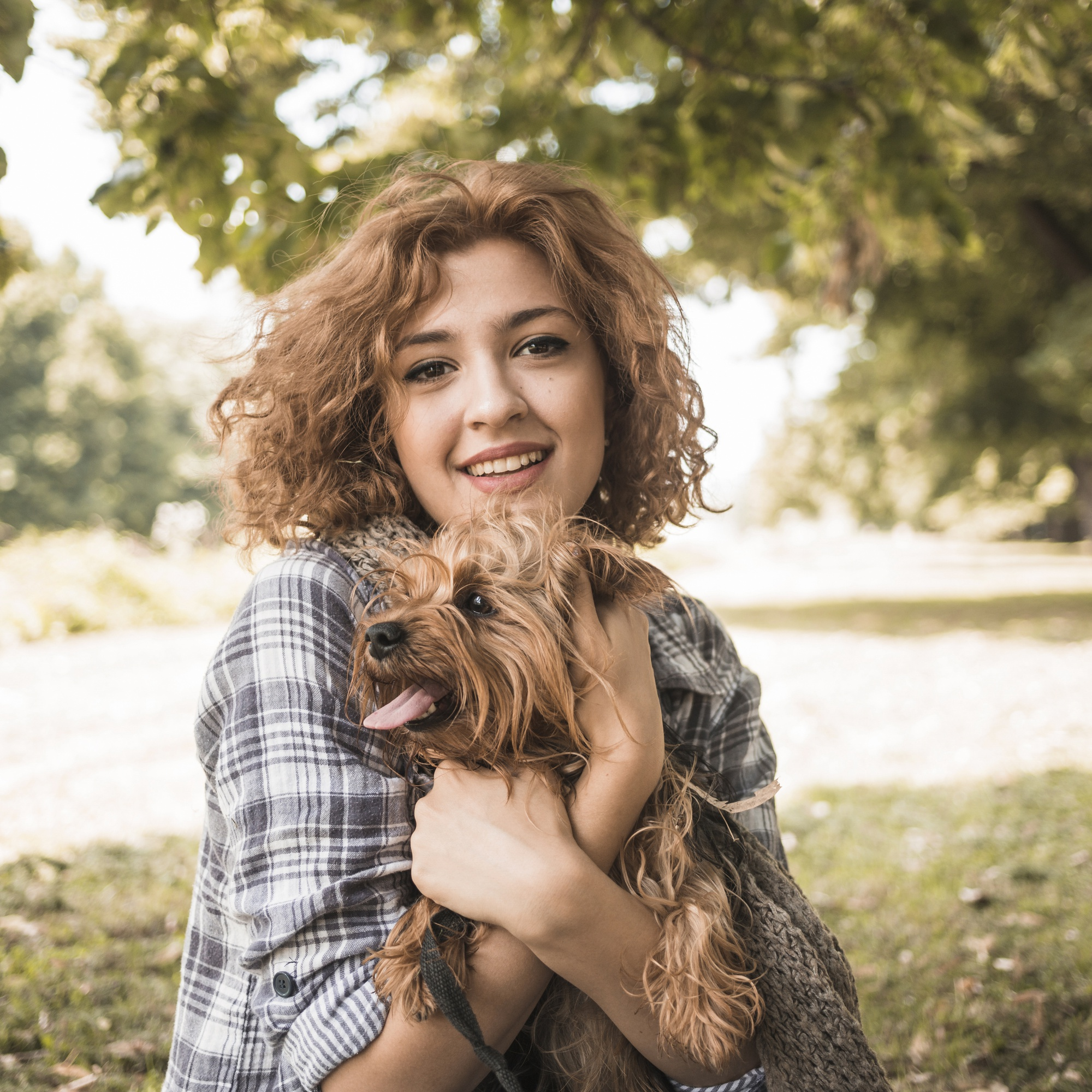 Smiling woman with dog in park