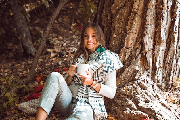Smiling woman with drink in forest
