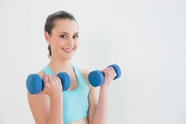 Smiling woman with dumbbells against wall