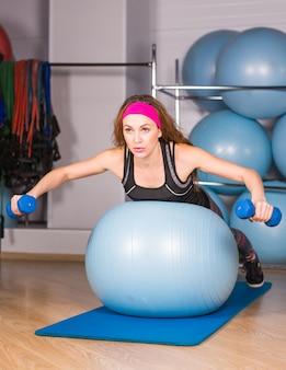 Улыбающаяся женщина с гантелями и мячом для упражнений в тренажерном зале и проекции