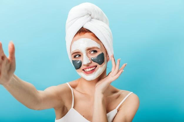 セルフィーを取るフェイスマスクと笑顔の女性。青い背景にポーズをとって頭にタオルを持った陽気な女性のスタジオショット。