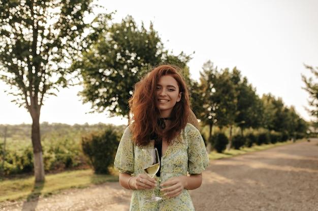 ふわふわの生姜髪と彼女の首に黒い包帯で笑顔の女性は、正面を見て、屋外のワインとガラスを保持している緑のモダンな服を着ています