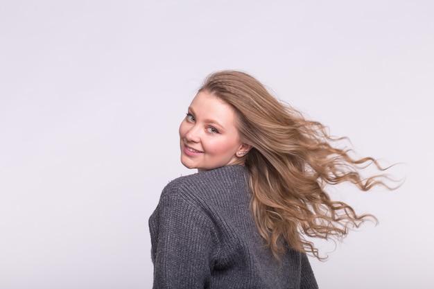 Улыбающаяся женщина с развевающимися волосами на белом с копией пространства.