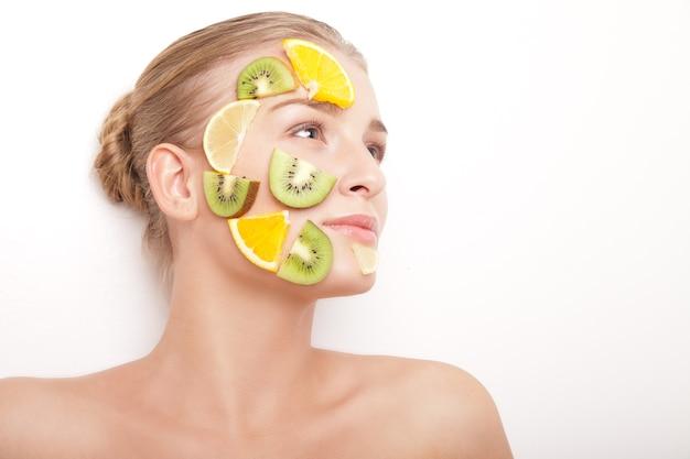 Улыбающаяся женщина с фруктовой маской на лице изолирована