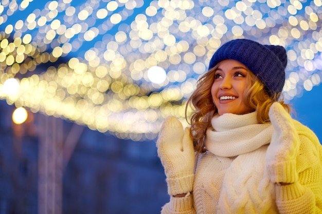 Smiling woman with garlands and holiday lights on festive christmas or new year fair.