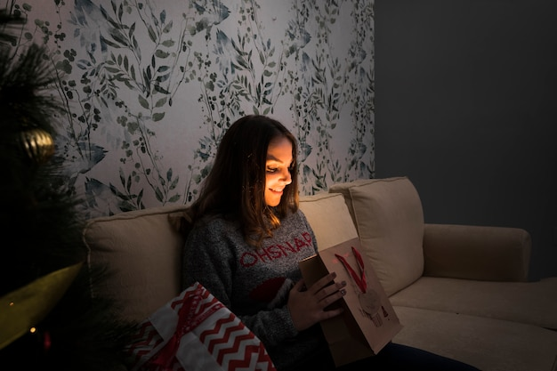 Smiling woman with gift packet on settee near christmas tree