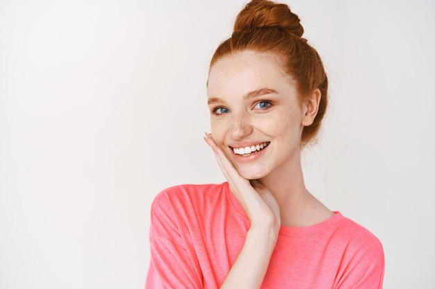 Smiling woman with ginger hair combed in messy bun, touching perfect skin and smiling, standing without makeup on white wall