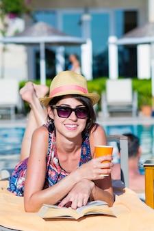 Donna sorridente con un bicchiere e un libro