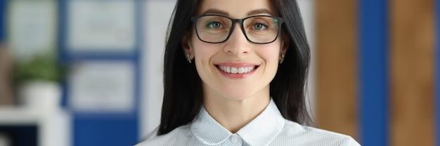 Улыбающаяся женщина в очках, держащая заявление о приеме на работу