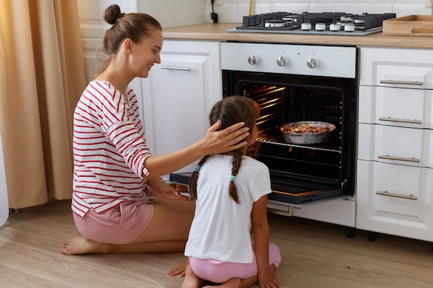 Smiling woman with hair ban touching her little daughter head while kid sitting backwards to camera and looking at oven with baking, female looking at child with love, cooking together.