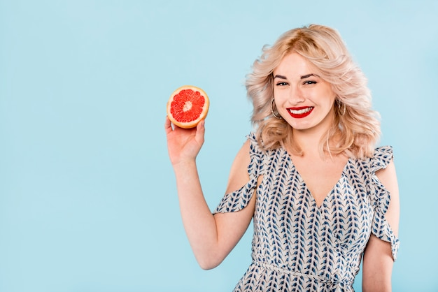 Smiling woman with half of grapefruit