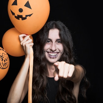 Smiling woman with halloween balloons pointing at you