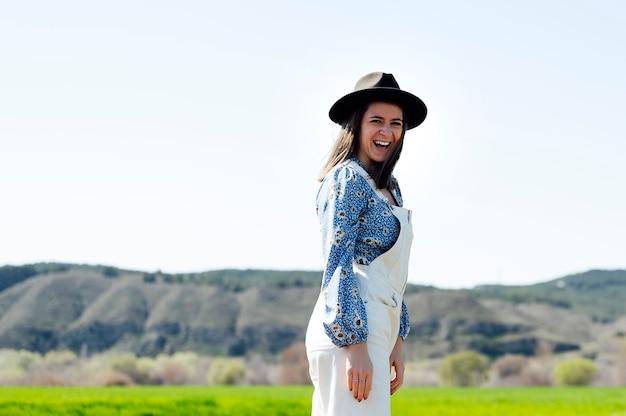 Улыбающаяся женщина в шляпе в солнечный день