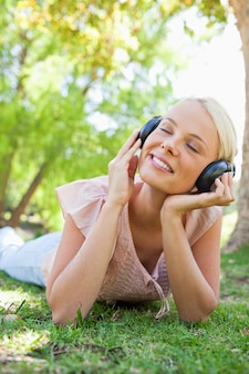 Smiling woman with headphones enjoying music on the lawn