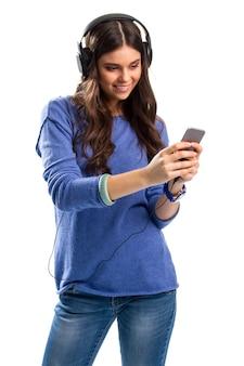 Улыбающаяся женщина с наушниками. леди смотрит на мобильный телефон. тонны новых впечатлений. новые прочные наушники.