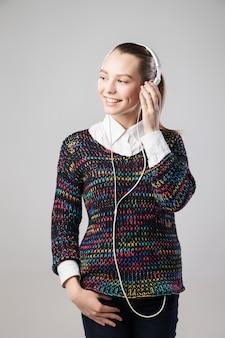 Улыбается женщина с наушниками, слушать музыку на плеере и глядя в сторону. музыкальный портрет девушки подростка на изолированном сером фоне