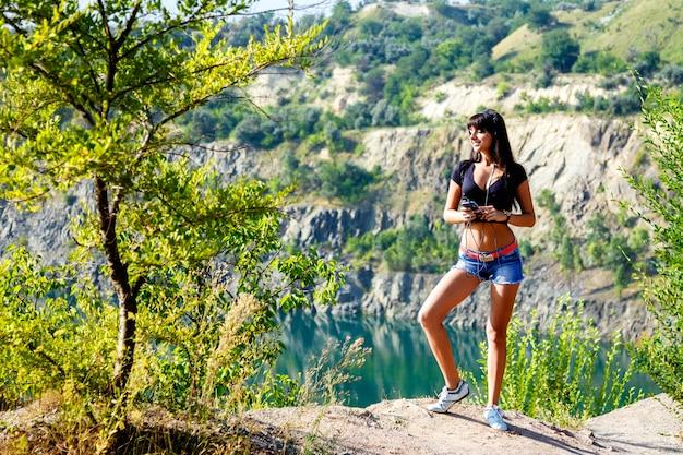 산 호수에서 음악을 듣고 헤드폰으로 웃는 여자