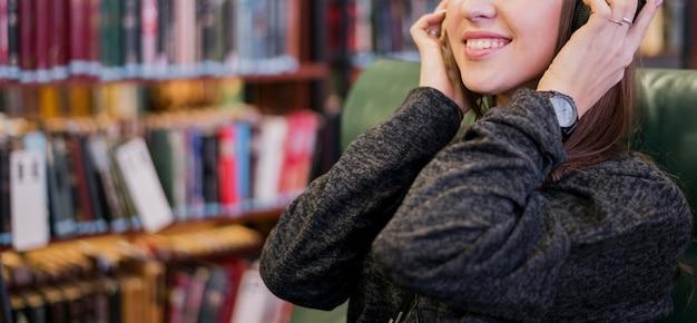 La donna sorridente con le cuffie si avvicina allo scaffale per libri