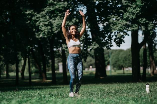 헤드폰을 끼고 피트니스 운동을 하는 웃는 여자