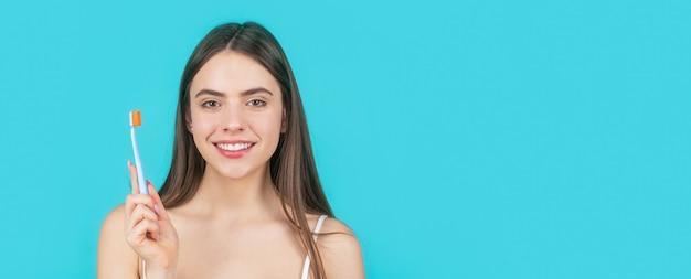 Улыбающаяся женщина со здоровыми зубами, держащая зубную щетку. молодая красивая девушка держит зубную щетку. счастливая девушка, ее зубы щеткой. гигиена полости рта.