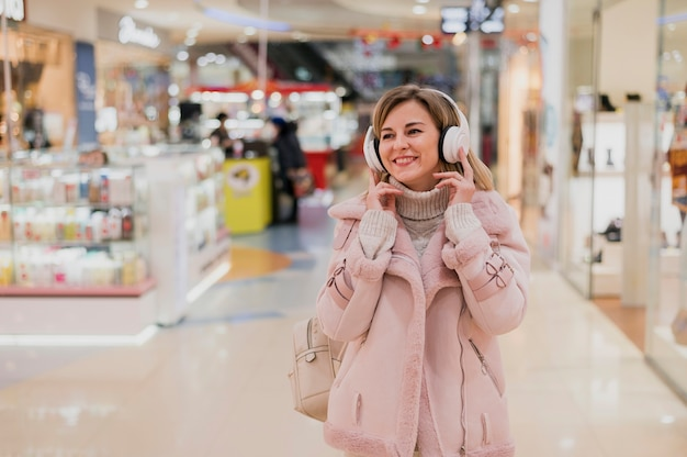 Улыбается женщина с heaphones в торговом центре