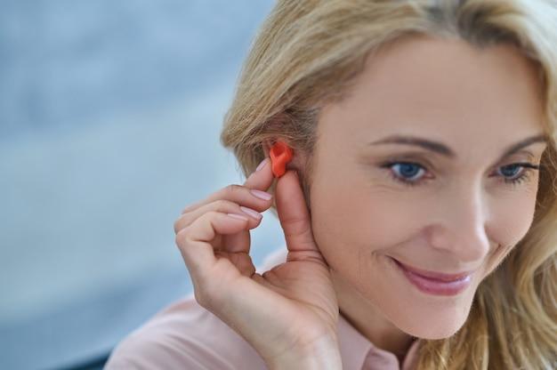 귀 근처 보청기를 가진 웃는 여자