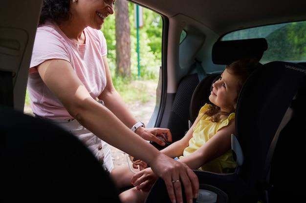 チャイルドシートにシートベルトで娘を固定しながら、愛らしい娘がお互いを見つめている笑顔の女性