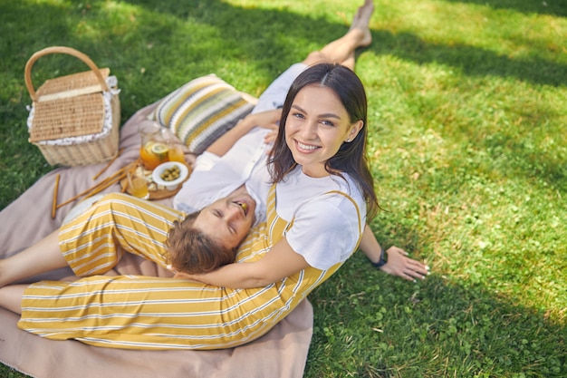 햇빛이 하루에 녹색 숲에서 피크닉에서 쉬고 그녀의 사랑스러운 남자와 웃는 여자