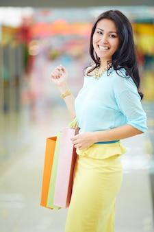 彼女の買い物袋を持つ笑顔の女性