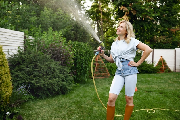 Smiling woman with hose watering trees in the garden. female gardener takes care of plants outdoor, gardening hobby, florist lifestyle and leisure