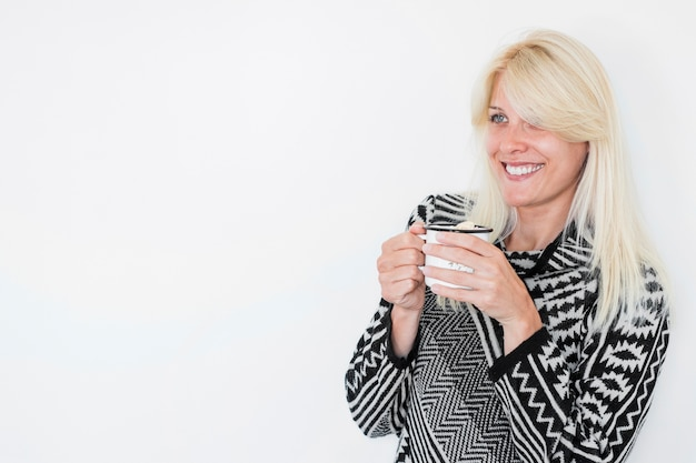 Smiling woman with hot beverage looking away