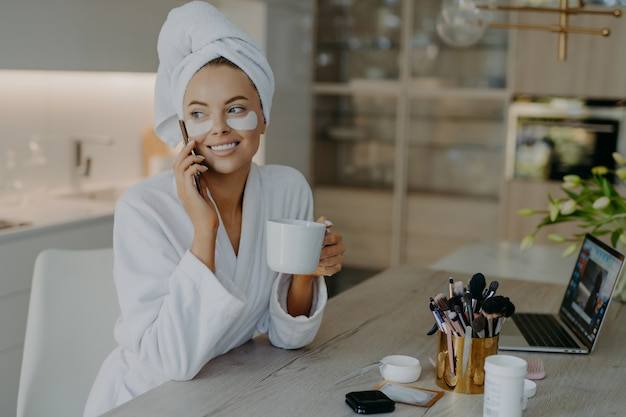 Smiling woman with hydrogel patches under eyes enjoys an hot drink tea while speaking on the phone
