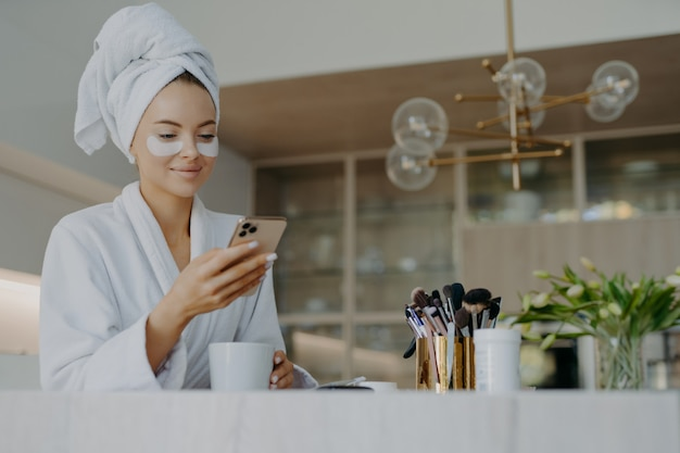Smiling woman with hydrogel patches under eyes enjoys an hot drink tea while using the mobile phone