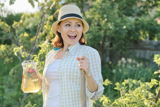 Smiling woman with jug of refreshing natural homemade drink in the summer garden.