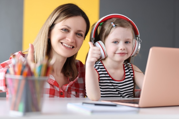 Smiling woman with little girl in headphones are engaged in online education on laptop