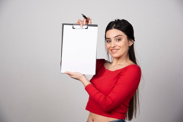 연필로 클립보드를 보여주는 긴 머리를 가진 웃는 여자.