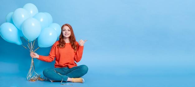 青い壁に隔離された、たくさんの気球を保持し、人差し指を脇に置いてカジュアルな服装で長い赤髪の笑顔の女性