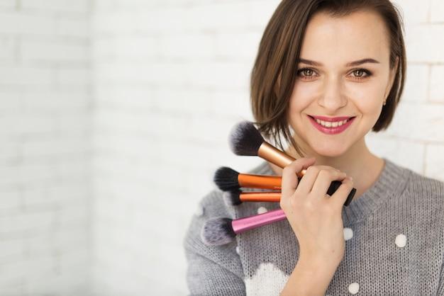 Sorridente donna con pennelli trucco