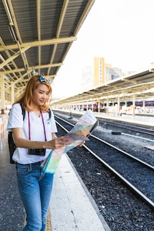 Smiling woman with map on platform