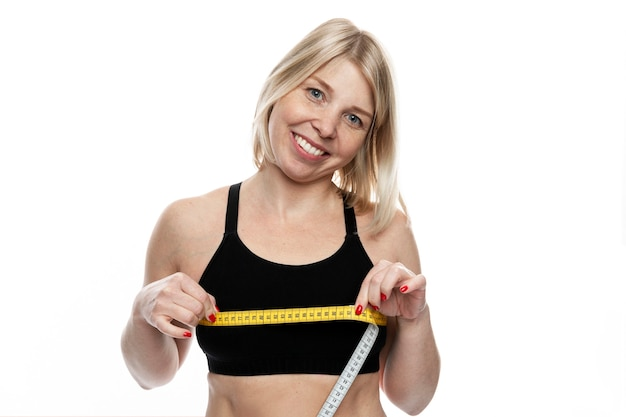 Smiling woman with a measuring tape on her chest. pretty blonde in a sporty black top. sports, diets and healthy lifestyles. isolated on white background.