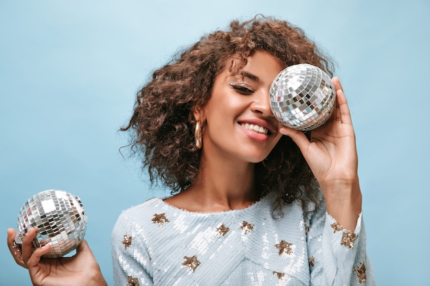 Smiling woman with modern makeup in trendy shine clothes with print stars and earrings smiling and posing with disco balls on blue wall..