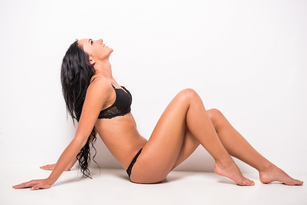 Smiling woman with perfect body is siting on the floor.