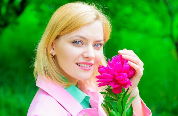 Улыбающаяся женщина с розовым цветком и размытым фоном растительности.