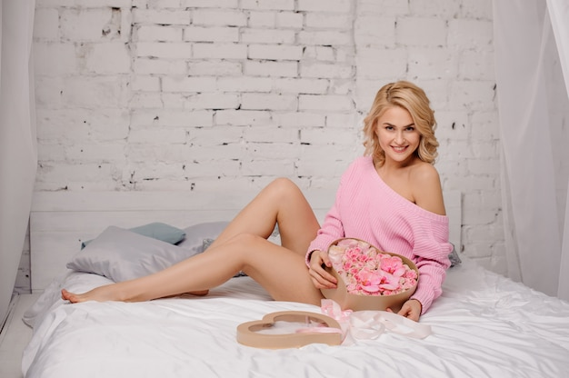 Smiling woman with pink shirt lying on the bed holding the heart shape box of rose colored flowers