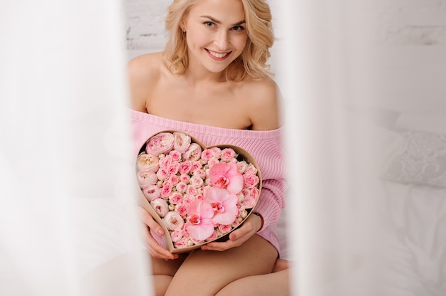 Smiling woman with pink shirt sitting on the bed holding the heart shape box of rose colored peonies, orchids and roses