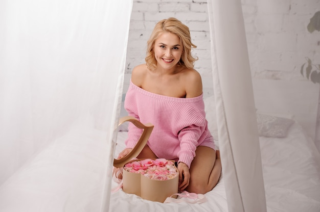 Smiling woman with pink shirt sitting on the bed opening the box of flowers