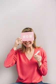 Smiling woman with pregnancy test and card