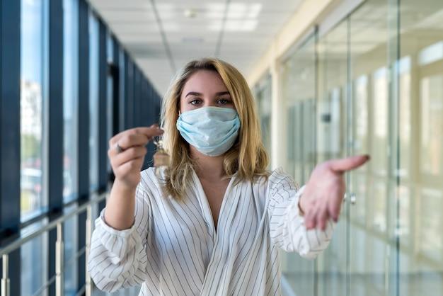 Улыбающаяся женщина с защитной маской с ключами от дома в современном бизнес-центре. концепция недвижимости и офиса